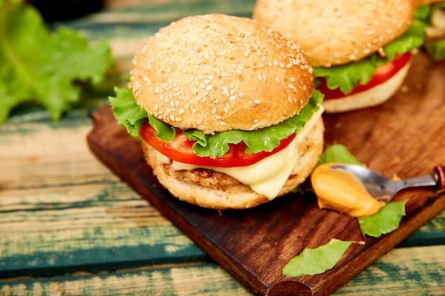 Burger de boeuf sur une table en bois isolée sur fond noir. Photo Premium