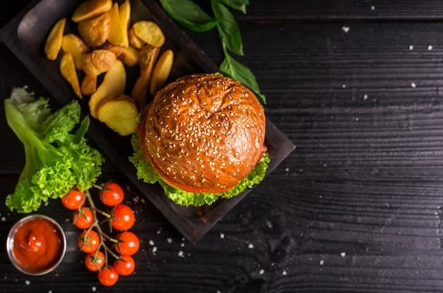 Burger classique à angle élevé avec frites et tomates cerises Photo gratuit
