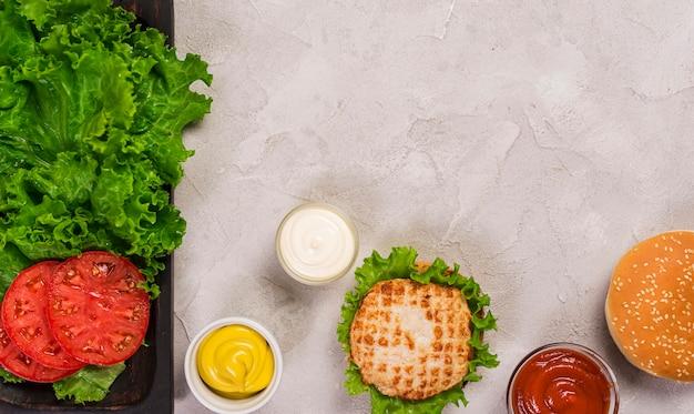 Burger classique vue de dessus avec des tranches de tomate et trempette Photo gratuit
