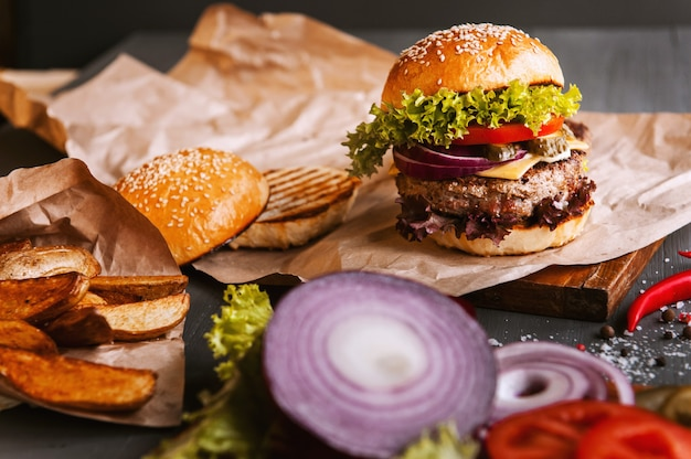 Burger fait maison délicieux sur une table en bois. à côté du composant à hamburger, plateaux en bois, pommes de terre frites et piment. Photo Premium
