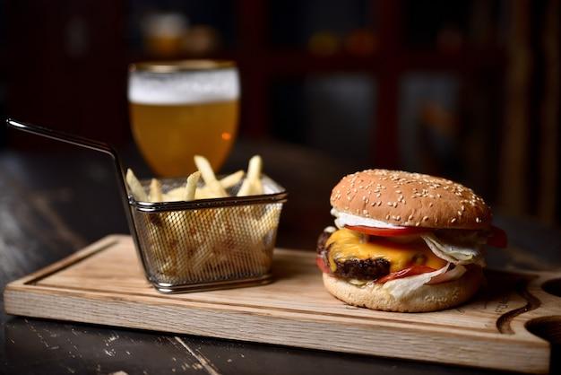 Burger avec des frites et de la bière sur une planche de bois Photo Premium