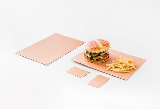 Burger et frites sur du papier brun sur fond blanc Photo gratuit