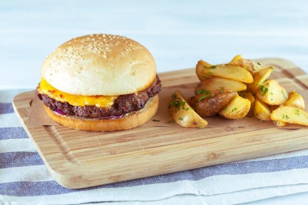 Burger et frites sur une table en bois Photo Premium