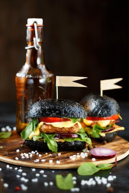 Burger noir avec côtelette, légumes verts, fromage, oignons et tomates et une bouteille de bière sur une plaque en bois Photo Premium