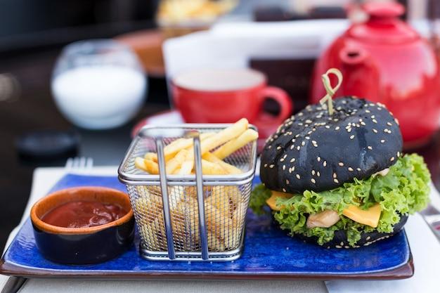 Burger noir avec pommes de terre frites et ketchup sur une assiette bleue Photo Premium