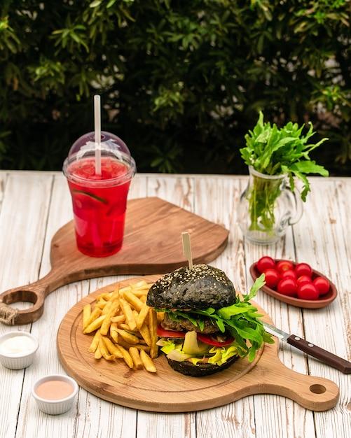 Burger noir servi avec des frites Photo gratuit