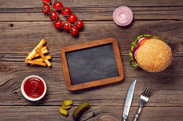 Burger à plat avec tableau Photo gratuit