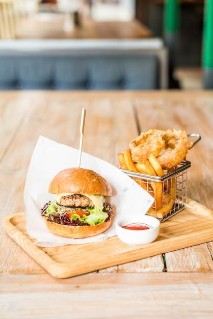 Burger de porc avec des oignons et des frites Photo Premium
