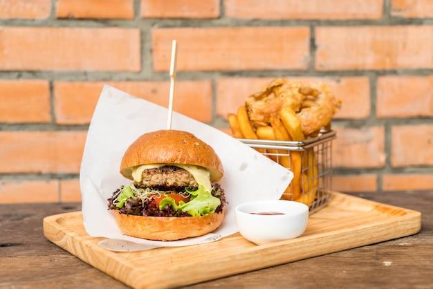 Burger de porc avec rondelles d'oignon et frites Photo Premium