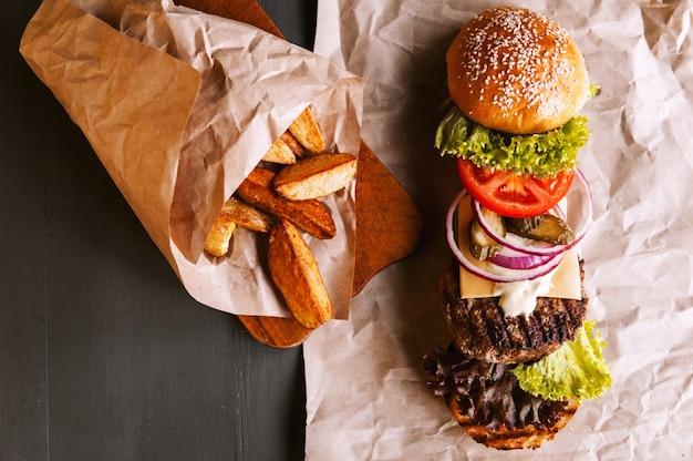 Burger se décomposa en ses composants sur du papier kraft posé sur une table en bois. paquet de puces. Photo Premium