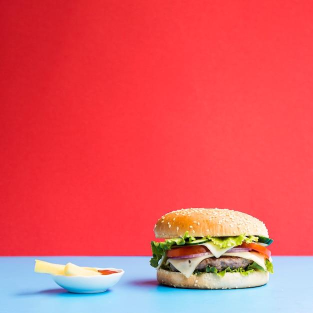 Burger sur une table bleue avec un fond rouge Photo gratuit