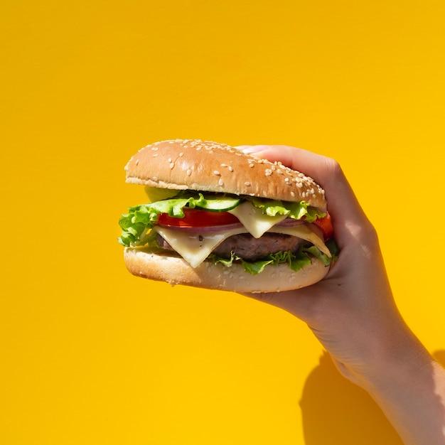 Burger tenu devant fond jaune Photo gratuit