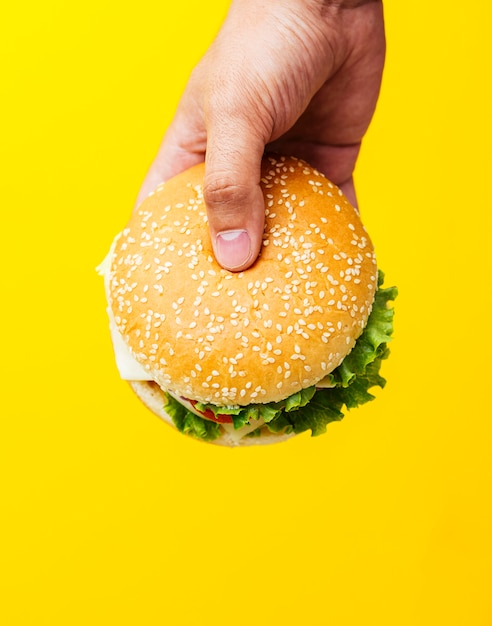 Burger Tenu Sur Fond Jaune Photo gratuit