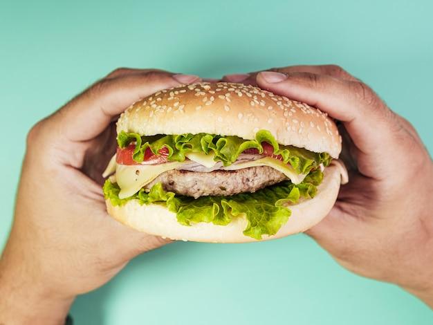 Burger tenue sur fond turquoise Photo gratuit
