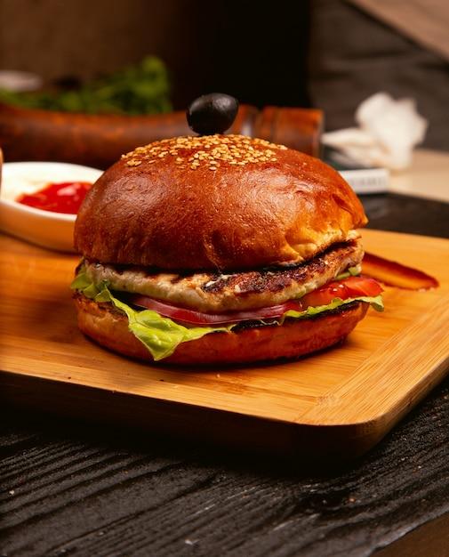 Burger à la viande de poulet avec des tranches de tomates et de la laitue servies avec du ketchup et de la mayonnaise sur une planche de bois Photo gratuit
