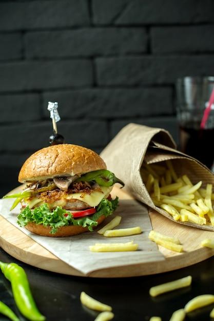 Burger Vue Latérale Avec Frites Et Poivron Vert Sur Tableau Noir Photo gratuit