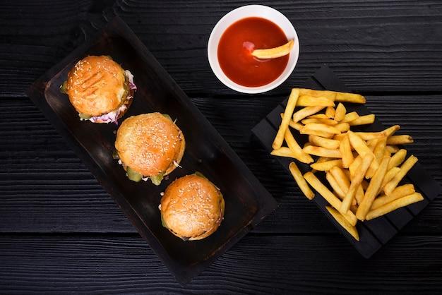 Burgers américains à angle élevé avec frites et sauce Photo gratuit