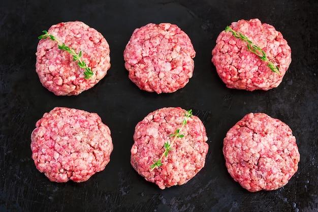 Burgers crus de boeuf bio sur fond noir, vue de dessus Photo Premium