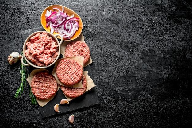 Burgers Crus Avec Du Boeuf Haché Et Des Oignons émincés Dans Des Bols. Sur Fond Rustique Noir Photo Premium