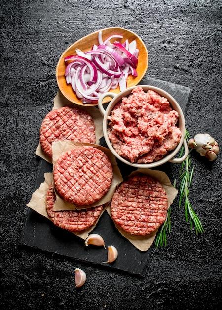 Burgers Crus Avec Du Boeuf Haché Et Des Oignons émincés Dans Des Bols. Sur Table Rustique Noire Photo Premium
