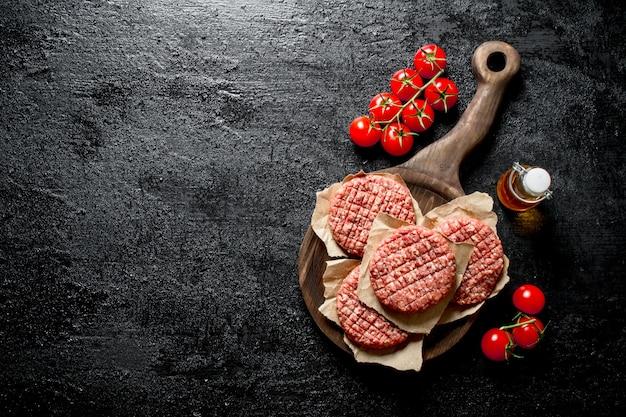 Burgers Crus Avec De L'huile Et Des Tomates Sur La Branche. Sur Fond Rustique Noir Photo Premium