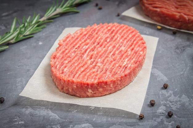 Burgers crus sur papier parchemin au romarin. fond de marbre gris. Photo Premium