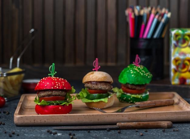 Burgers de pain de pain brun et vert rouge dans un plateau. Photo gratuit