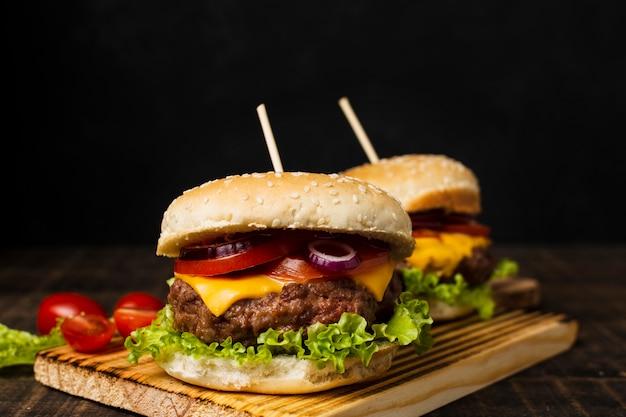 Burgers sur planche à découper avec fond noir Photo gratuit