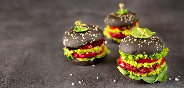 Burgers végétaliens noirs avec des galettes de betterave sur une surface sombre Photo Premium