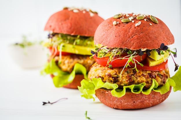 Burgers végétaliens roses avec côtelette de haricots, avocat et choux sur blanc Photo Premium