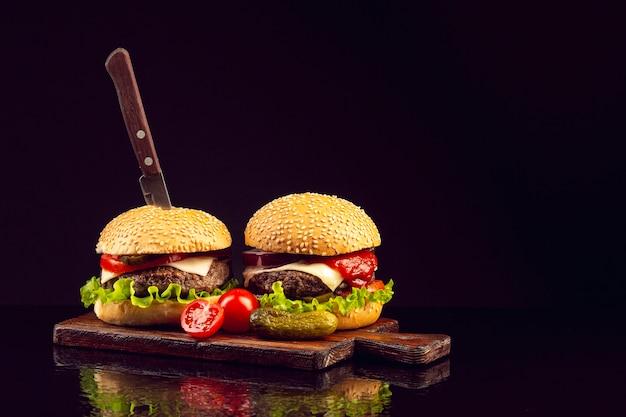 Burgers vue de face sur une planche à découper Photo gratuit