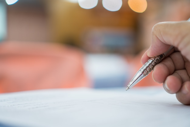 Business concept: homme d'affaires à la main tenant un stylo argenté pour prendre des notes sur des documents blancs Photo Premium