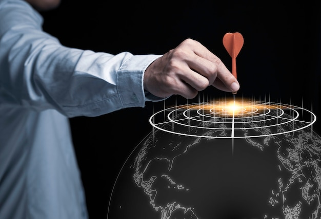 Businessman Hand Holding And Trowing Red Dart To Target Board On Black Background And World Map. Business And Investment Target Concept. Photo Premium