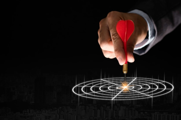 Businessman Hand Holding And Trowing Red Dart To Target Board On Black Background.business And Investment Target Concept. Photo Premium