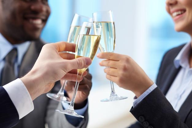 Businesspeople célébrant l'accord avec le champagne Photo gratuit