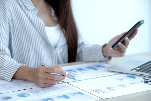 Businesswoman Hand Holding Pen Et Analyse Le Graphique Avec Ordinateur Portable Au Bureau Pour Définir Des Objectifs Commerciaux Difficiles Et Planifier Pour Atteindre Le Nouvel Objectif. Photo Premium