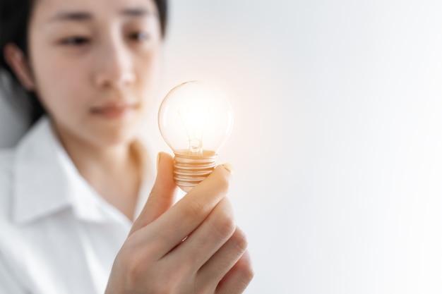 Businesswoman Holding Ampoule Rougeoyante, Sur Fond Blanc Photo Premium