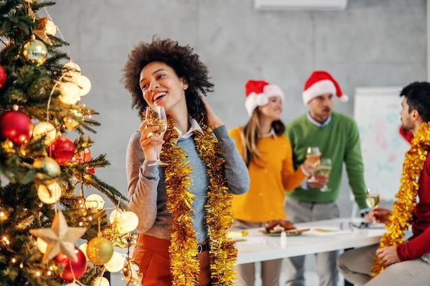 Businesswoman Holding Champagne La Veille De Noël Dans Son Entreprise. En Arrière-plan, Ses Collègues. Photo Premium