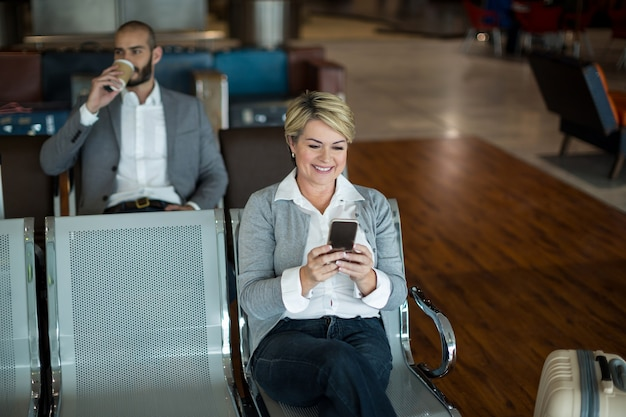 Businesswoman Using Mobile Phone Dans La Zone D'attente Photo gratuit