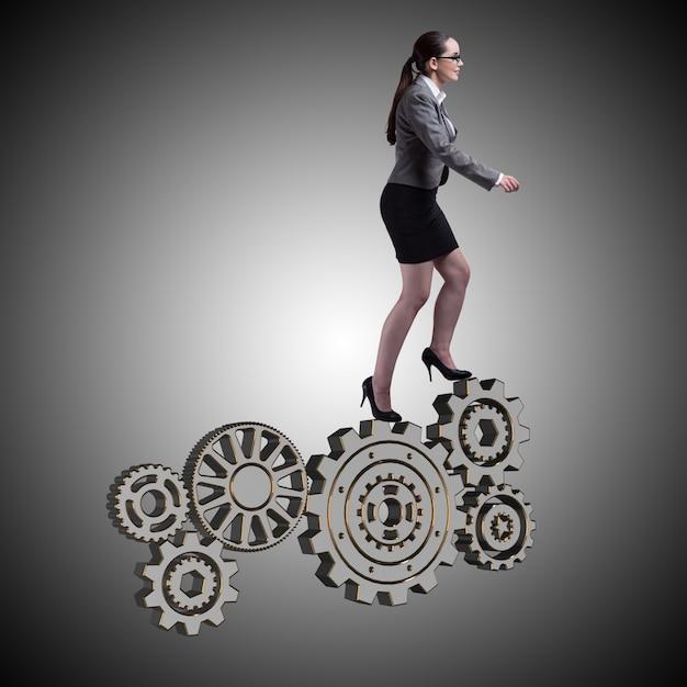 Busineswoman avec roues dentées dans le concept de travail d'équipe Photo Premium
