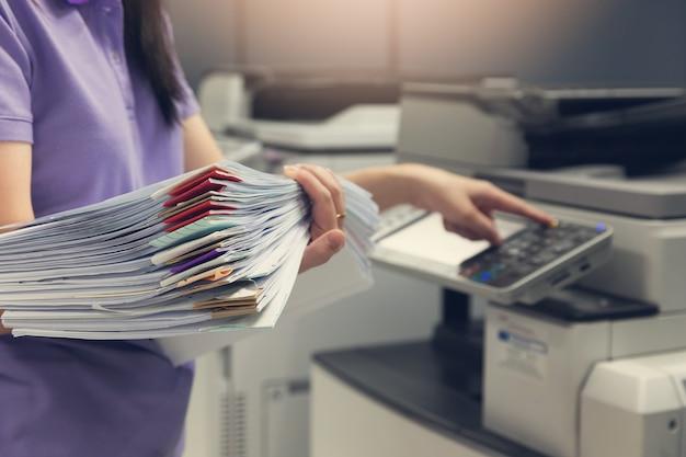 Bussinesswoman utilisant une machine à copier pour copier des documents. Photo Premium