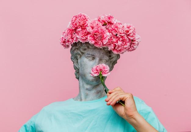 Buste antique de mâle avec bouquet d'oeillets dans un chapeau Photo Premium