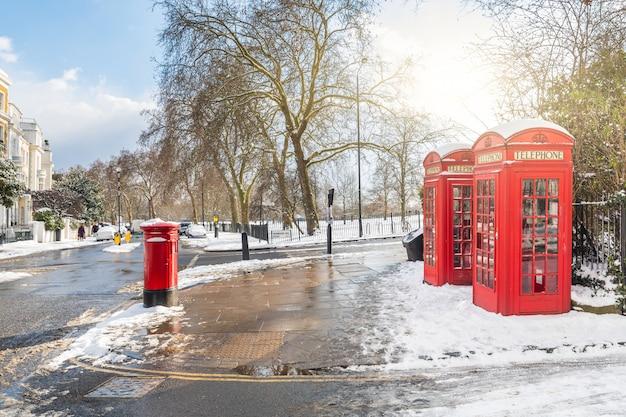 Cabines téléphoniques rouges à londres avec neige Photo Premium