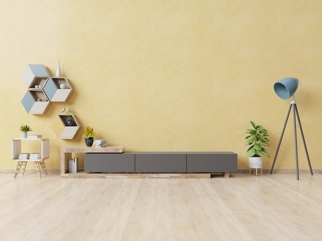 Cabinet pour la télévision ou placer un objet dans le salon moderne avec lampe, table, fleur et plante sur un mur jaune. Photo Premium