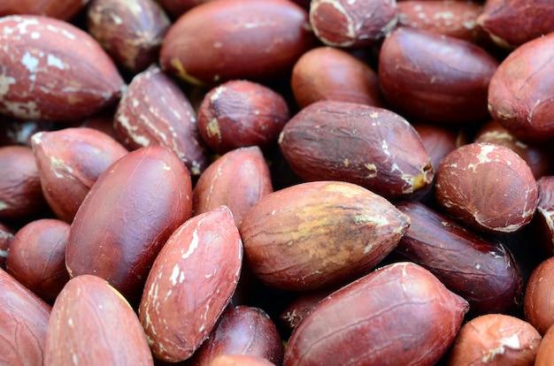 Cacahuète. beaucoup de petites noix jaunes à la peau brune. texture de fond Photo Premium