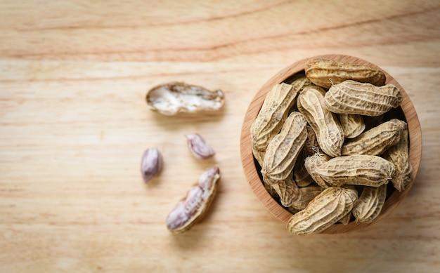 Cacahuète dans un bol en bois et vue de dessus en bois / arachides bouillies Photo Premium