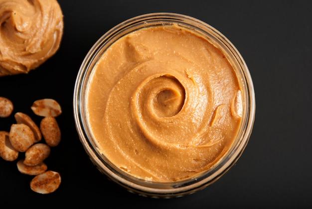 Cacahuètes et beurre de cacahuète frais, fond noir. Photo Premium
