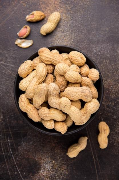 Cacahuètes en coquille dans un bol sur dark Photo Premium