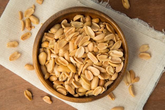 Cacahuètes grillées dans un bol en bois mettant sur lin et fond en bois. Photo Premium