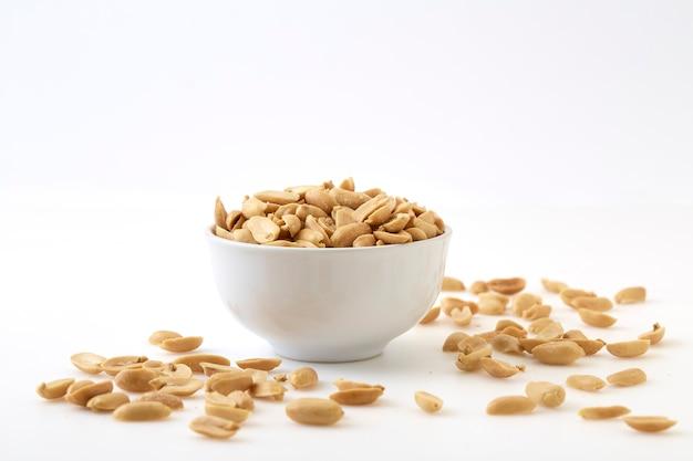 Cacahuètes grillées et sel dans un bol Photo Premium